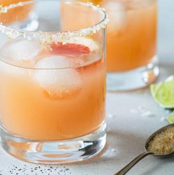 Close up of two grapefruit margaritas in salt rimmed glasss