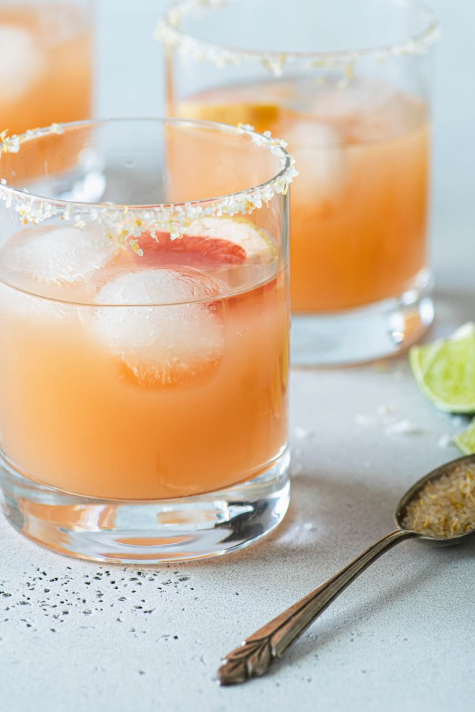 Close up of two grapefruit margaritas in salt rimmed glasss