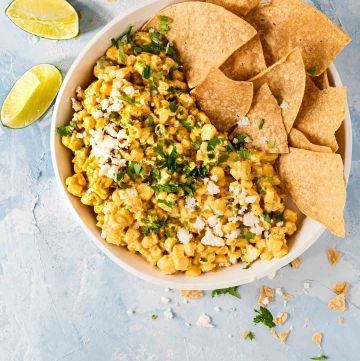Overhead shot of Mexican Street Corn dip in a white bowl with tortilla chips