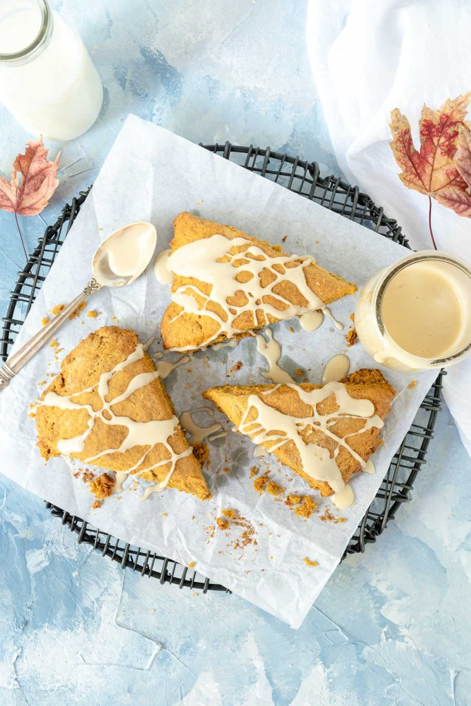 Three pumpkin scones drizzled with glaze on a black wire rack
