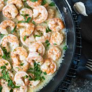 Overhead shot of garlic butter shrimp in a dark skillet