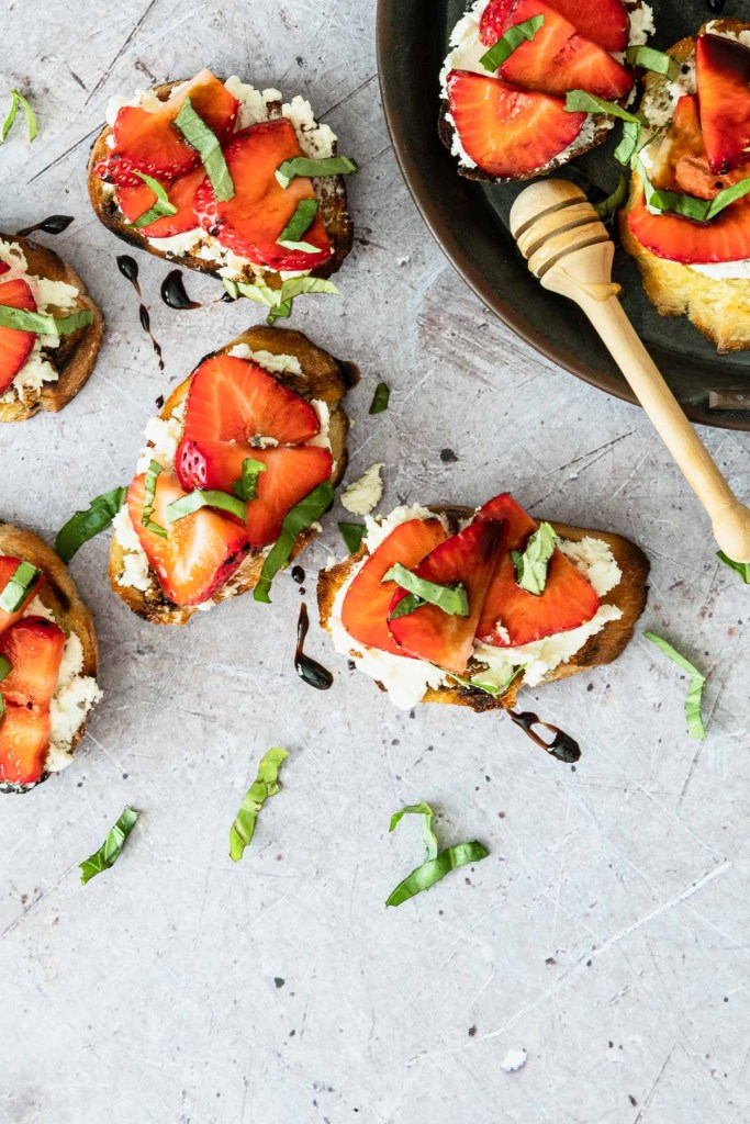 Overhead shot of toasted bread topped with goat cheese, strawberries, basil and balsamic glaze