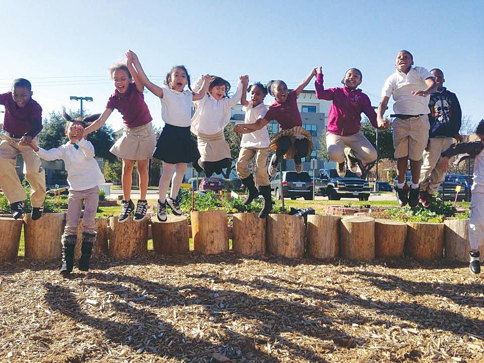 kids jumping on logs during garden education class in Houston