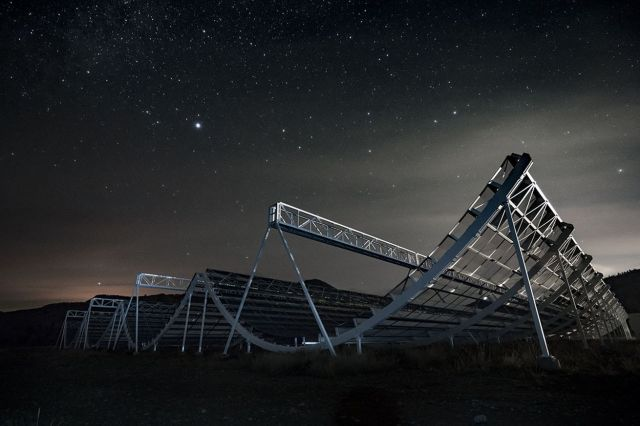 <em>The CHIME telescope looking up at the night sky.</em>