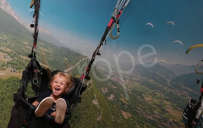 Image d'une enfant dans une nacelle de parapente
