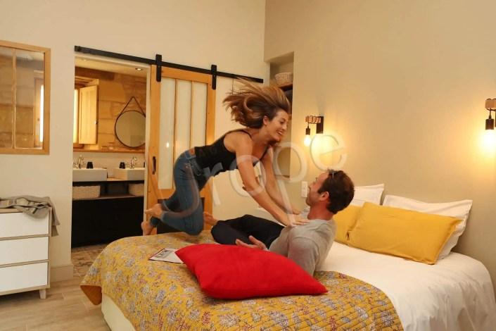 Photo d'une femme qui saute sur son homme sur un lit à Sarlat pour illustrer un gîte