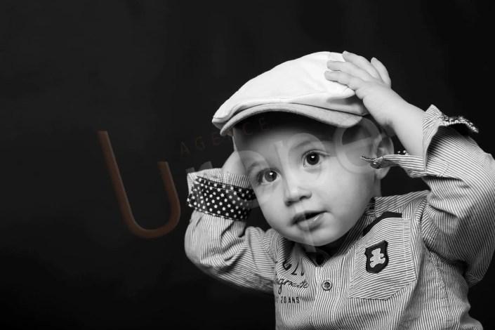 Photo d'un bébé en noir et blanc avec une casquette