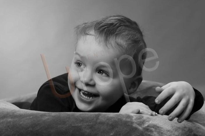 Photographe portraitiste avec un enfant en noir et blanc qui rit allongé sur un coussin