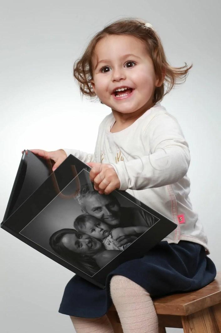 Photo d'une petite fille qui lit un livre sur fond blanc