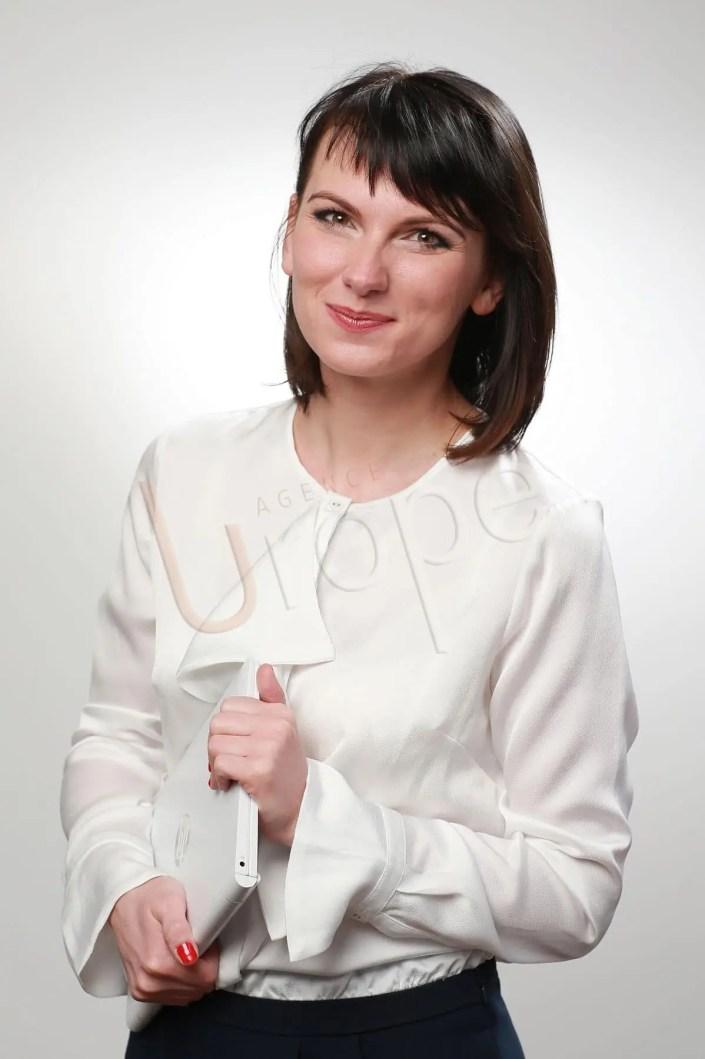 Photographie CV en studio pour les réseaux sociaux d'une jeune femme d'affaires avec un fond blanc