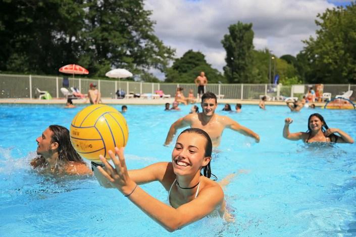 Photo d'une jeune femme qui joue au ballon dans une piscine de camping