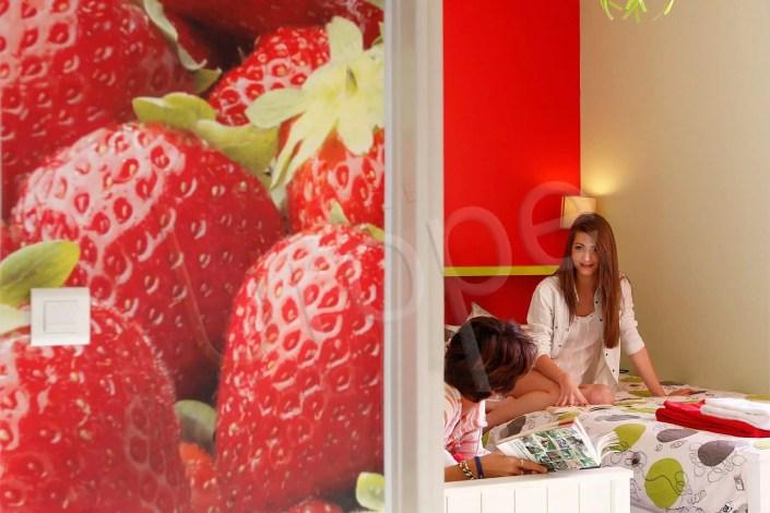 Photographie originale d'une chambre d'hôtel avec 2 femmes assises et des fraises sur le mur