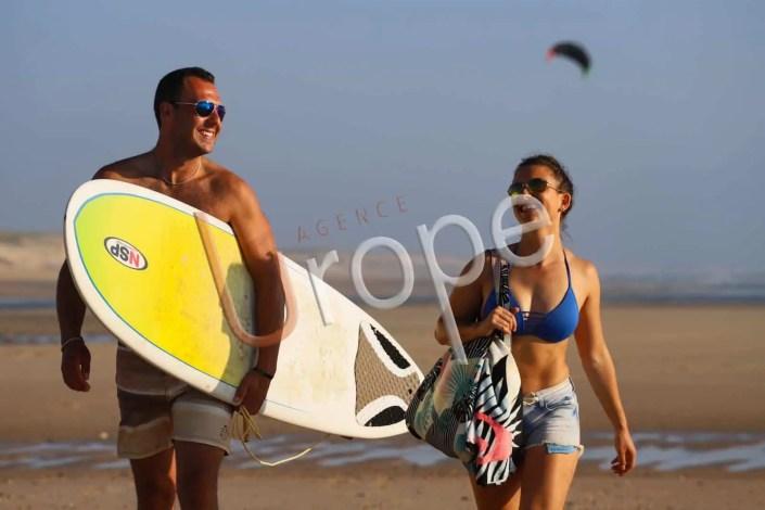 Couple qui part surfer sur l'Océan Atlantique