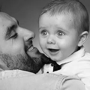 Photo de famille avec un nouveau-né étonné en noir et blanc sur l'épaule de son papa