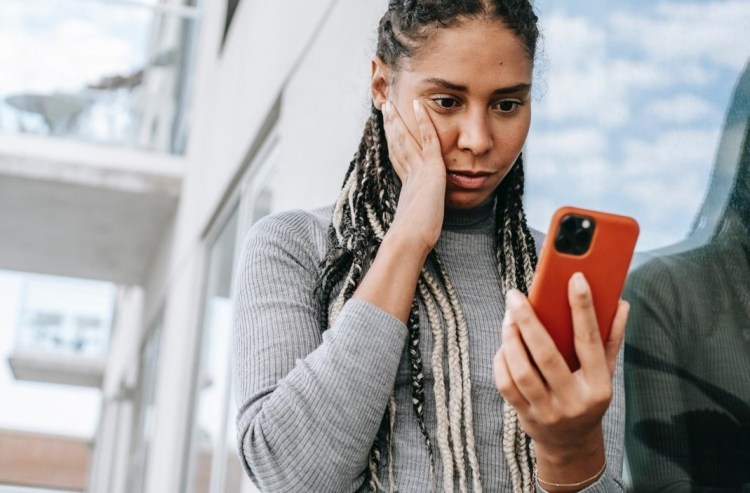 worried women looking at cell phone - hack