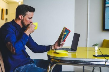 man drinking coffee with book and laptop