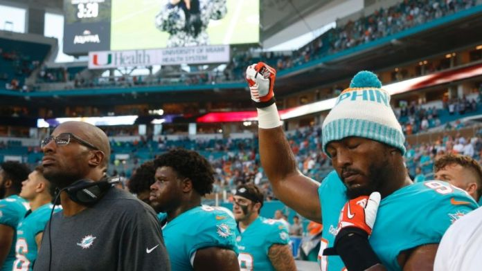 Miami Dolphins defensive end Robert Quinn (94) raises his right fist during the singing of the national anthem, before the team's NFL preseason football game against the Tampa Bay Buccaneers, Thursday, Aug. 9, 2018, in Miami Gardens, Fla. (AP Photo/Wilfredo Lee) (Copyright 2018 The Associated Press. All rights reserved.)