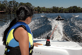 Female passenger on powerboat watching male tubing