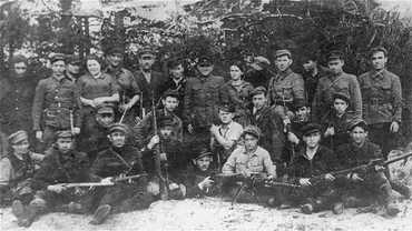 Group portrait of members of the Kalinin Jewish partisan unit (Bielski group) on guard duty at an airstrip in the Naliboki Forest. 1941-1944.