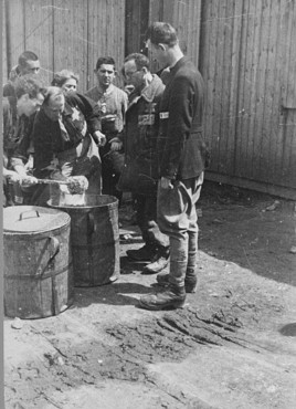Prisoner forced laborers crowd around containers of food. Plaszow labor camp, Poland, 1943-1944.