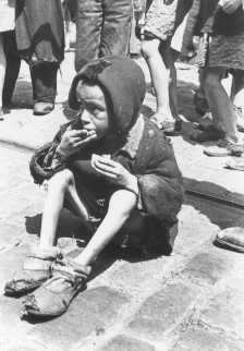 Un enfant épuisé mange dans les rues du ghetto de Varsovie. Varsovie, Pologne, entre 1940 et 1943.