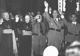 Clérigos católicos y oficiales nazis, entre ellos Joseph Goebbels (extrema derecha) y Wilhelm Frick (segundo, de derecha a izquierda), hacen el saludo nazi. Alemania, fecha incierta.