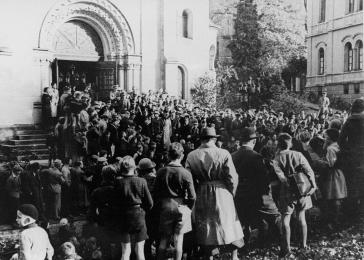 Hundreds of Germans congregated in front of the synagogue watch as Jews are escorted into the synagogue under SS guard.