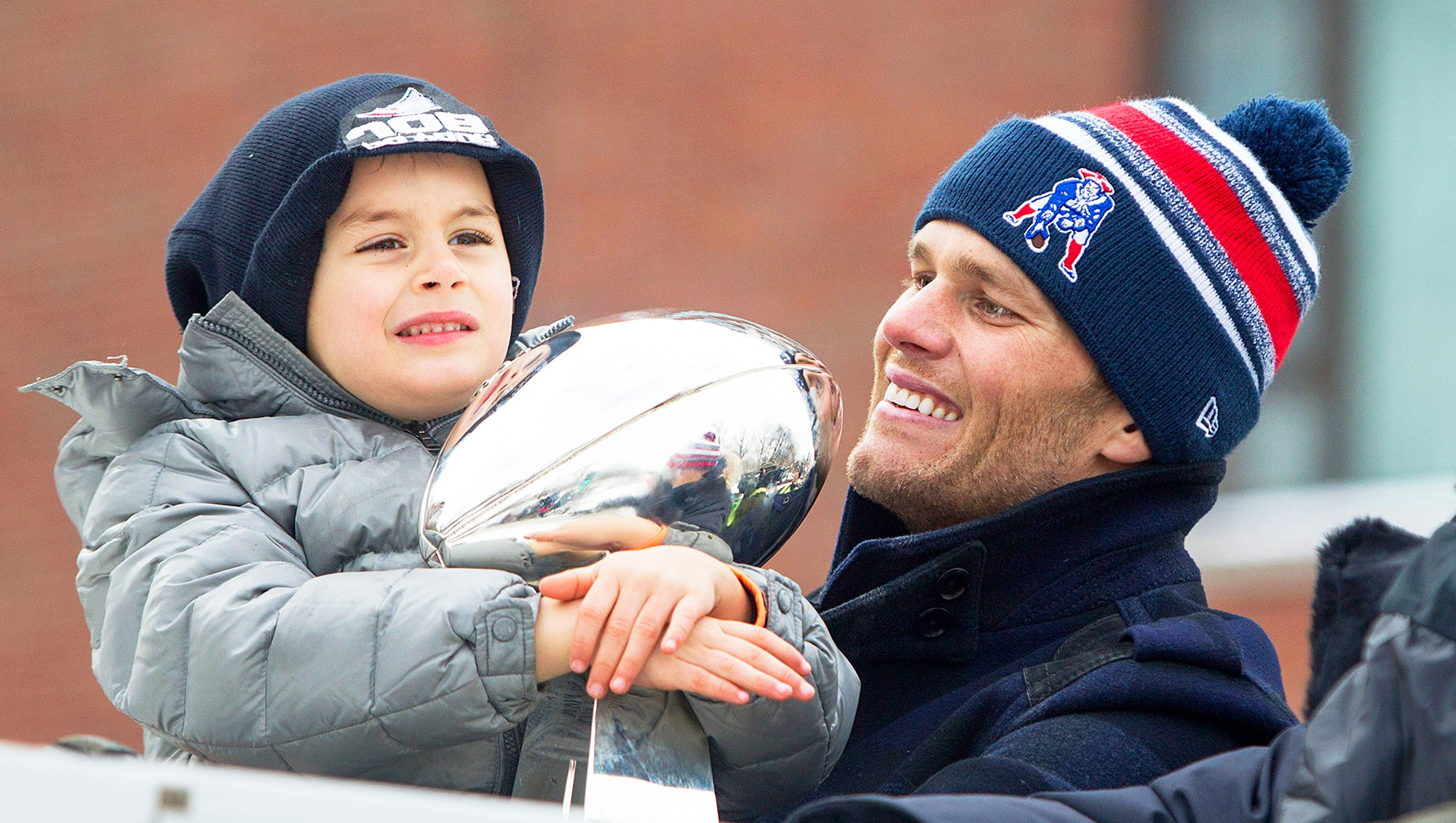 Tom Brady and son Benjamin holds the Lombardi trophy during the New England Patriots Victory 2015 Parade in Boston, Massachusetts.