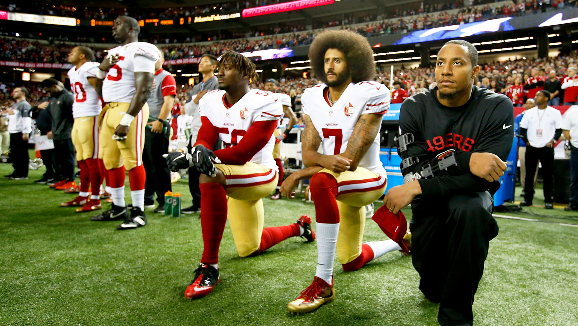Colin Kaepernick #7 of the San Francisco 49ers kneel on the sideline, during the anthem, prior to the game against the Atlanta Falcons at the Georgia Dome on December 18, 2016 in Atlanta, Georgia.