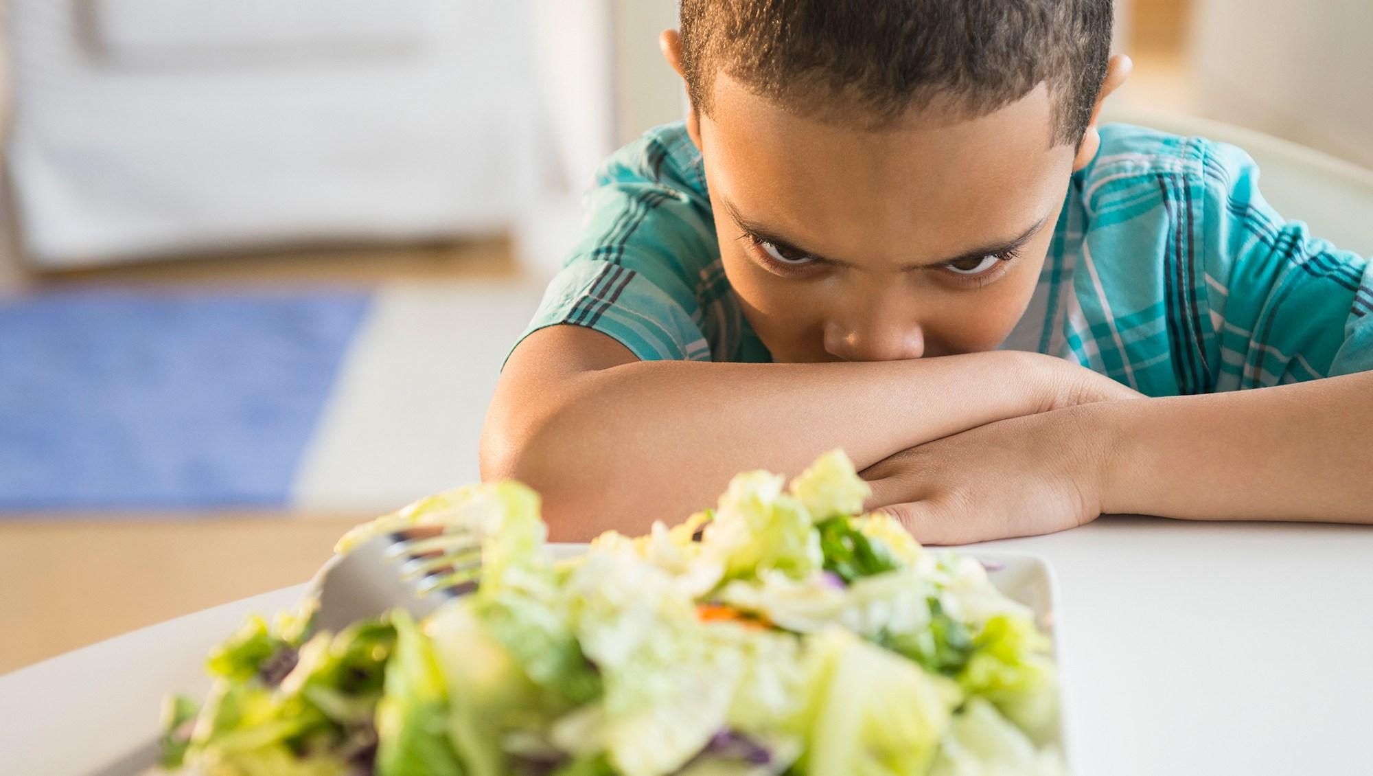 boy refusing to eat salad