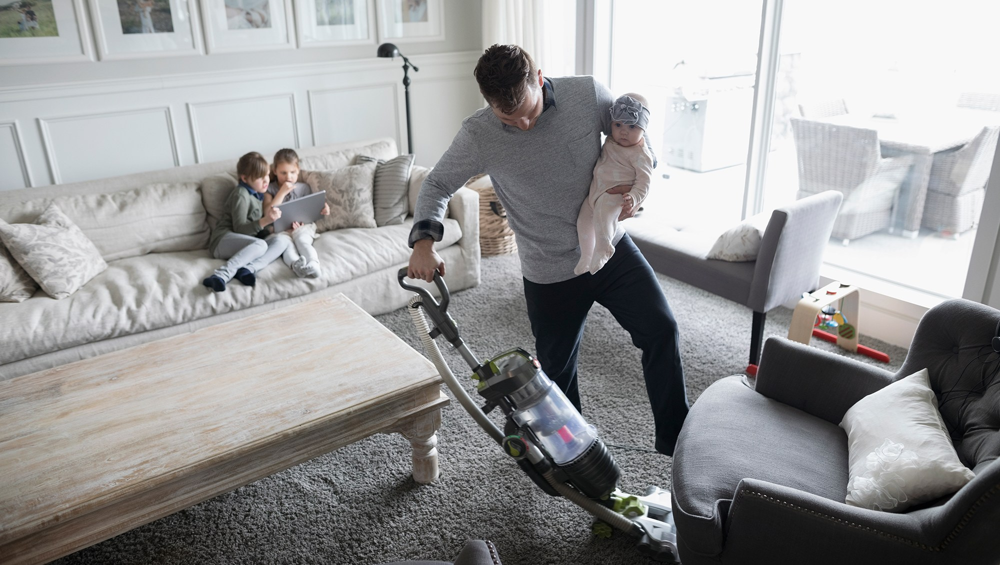 Father holding baby daughter and vacuuming living room