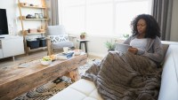 Relaxed woman with blanket using digital tablet on living room sofa