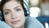 Woman wearing headphones and using neck pillow