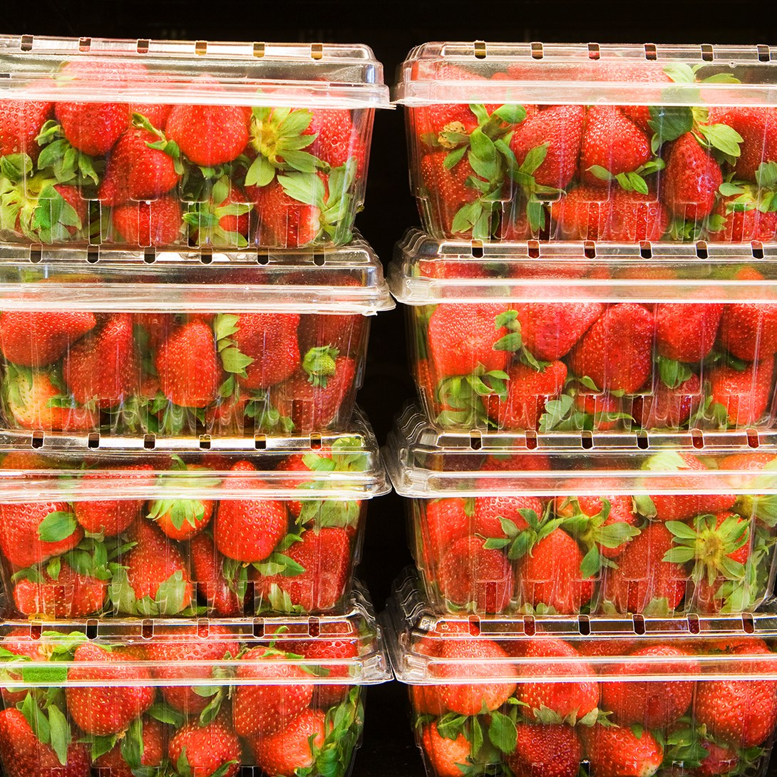Strawberries in containers on supermarket shelf.