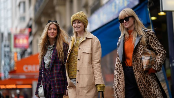 three women walking wearng coats. One woman is wearing a khaki coat, another is wearing a plaid blazer coat another is wearing a leopard print coat. All are smiling.