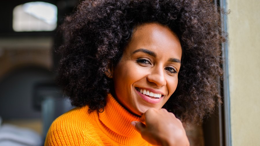 woman with big curly hair smiling while sitting down wearing a bright orange sweater