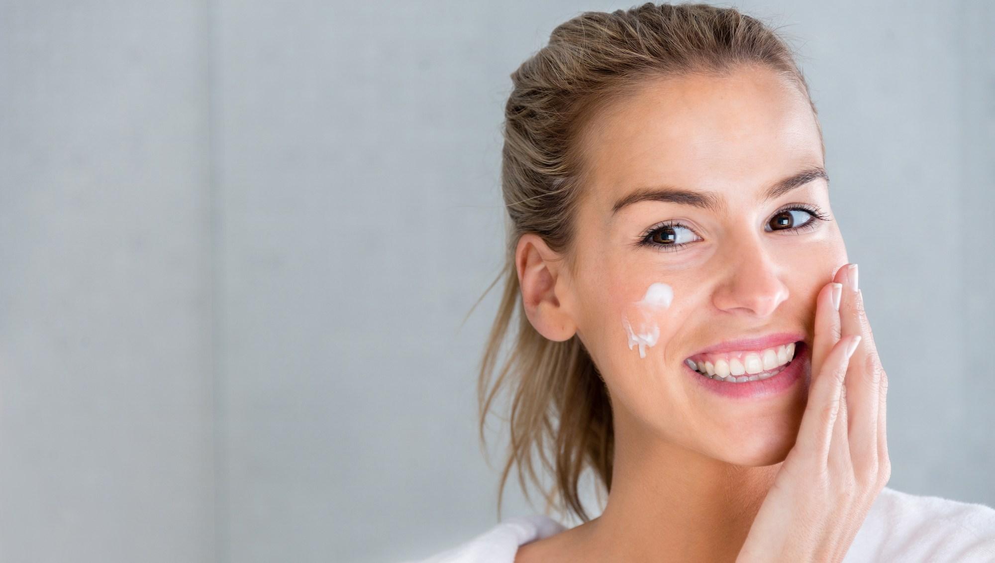 Beauty portrait of a woman using moisturising cream