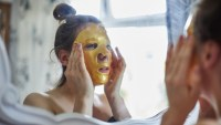 Woman applying a gold face mask in the mirror