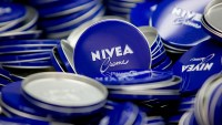 Lids of Nivea Creme skin care lotion tins sit in the production center at the headquarters of Beiersdorf AG in Hamburg, Germany, on Thursday, Feb. 12, 2015.
