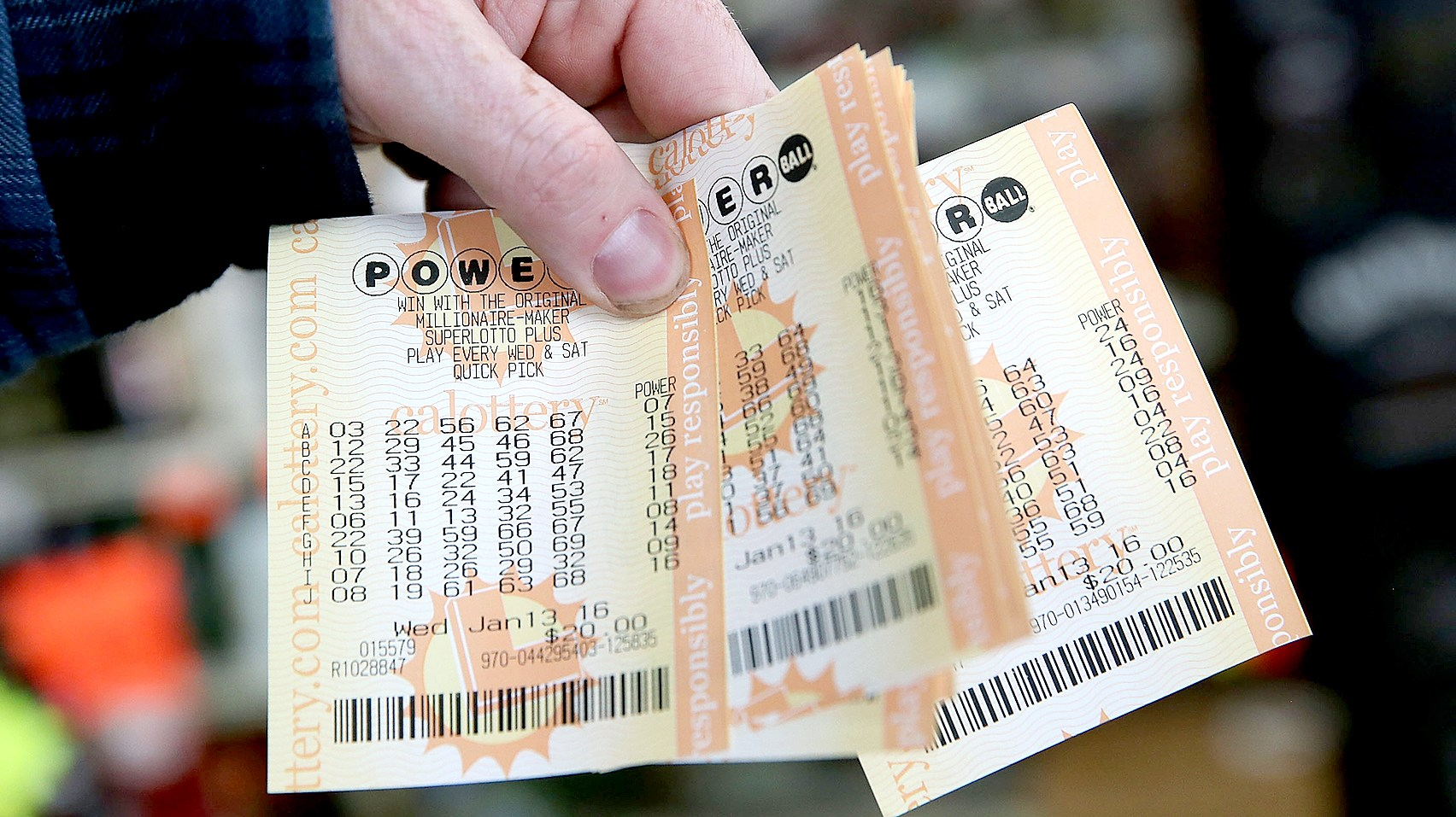 A customer holds a handful of Powerball tickets at Kavanagh Liquors on January 13, 2016 in San Lorenzo, California.