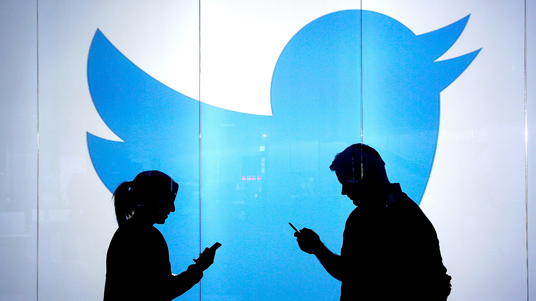 People are seen as silhouettes as they check mobile devices whilst standing against an illuminated wall bearing Twitter Inc.'s logo.