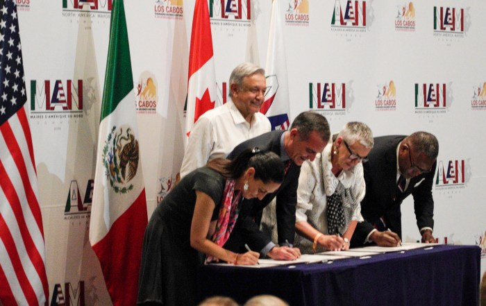 Mexico President AMLO looks on as mayors sign the declaration at the first North America Mayors Summit.