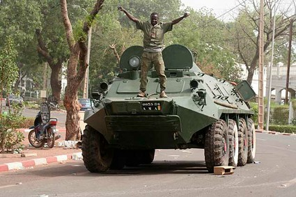 A soldier poses atop a military vehicle, as it stands guard outside the presidential palace following a military coup in Bamako, Mali. The whereabouts of Mali's president Amadou Toumani Toure were unknown Friday, a day after mutinous soldiers declared a coup, raising fears and prompting uncertainty in a West African nation that had been one of the region's few established democracies.