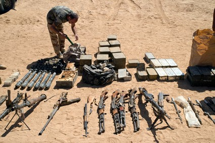 A French soldier inspecting weapons and ammunitions found in the Mettatai region in northern Mali on March 14, 2013.