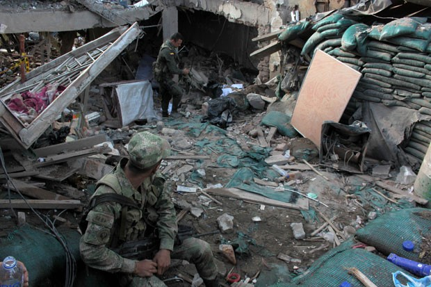 A police officer, background, inspects the wreckage of the destroyed police station of Inza, in Colombia's southern Cauca state, Saturday, Dec. 7, 2013. The Colombian Army said that five members of the military, two civilians and a police officer were killed when rebels of the Revolutionary Armed Forces of Colombia, FARC, threw artisanal mortar at the post, destroying that and several other buildings. Sitting, foreground left, is a soldiers.