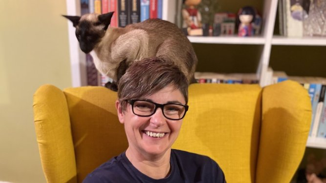 Louise Solomon sitting at home with a cat on her chair