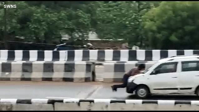 Car drives along road with man clinging to bonnet