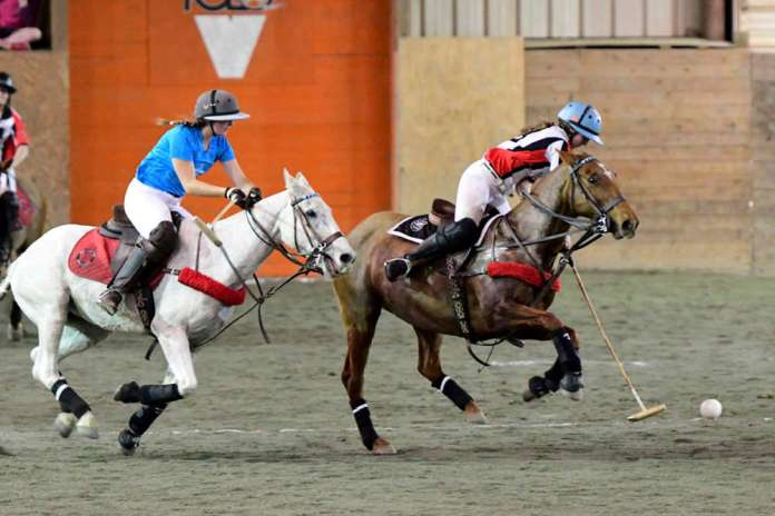 Maryland Polo Club's Maddie Grant carries the ball down the arena on the nearside, Central Coast Polo Club's Petra Teixeira on defense.