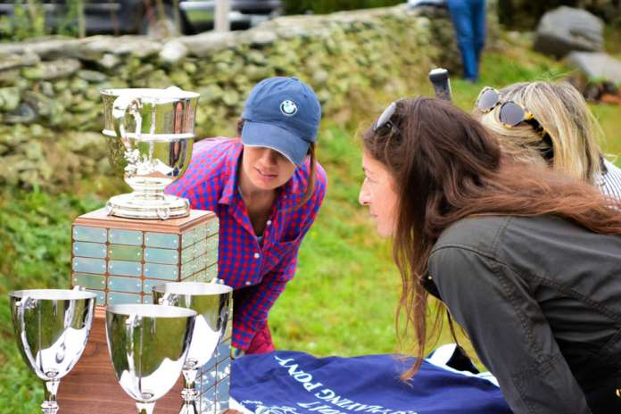 Polo fans and competitors inspect the inscriptions on the George Carter Sherman Memorial Indoor Polo Cup.
