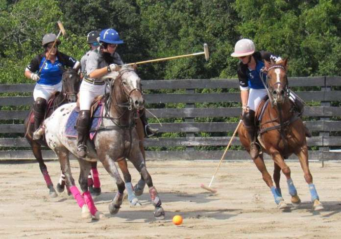 Rebellis' Kasey Morris reaches for the ball alongside Old Farm Vet's Sierra Goff on Best Playing Pony Pandora.